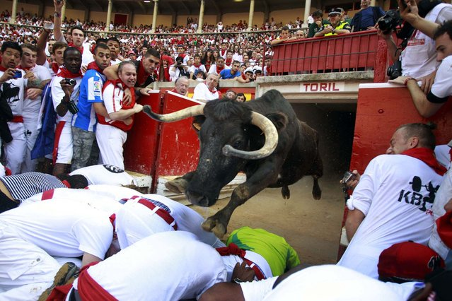 A fighting cow leaps over revelers into the bull ring after the fourth running of the bulls at the San Fermin festival in Pamplona July 10, 2013. (Photo by Joseba Etxaburu/Reuters)