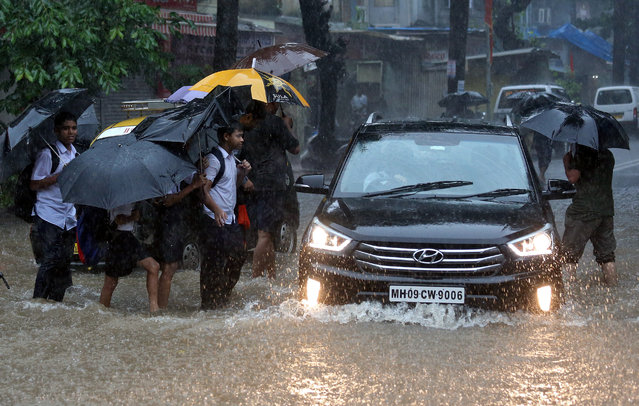 School children wade through a waterlogged road during heavy rains in Mumbai, July 9, 2018. (Photo by Francis Mascarenhas/Reuters)