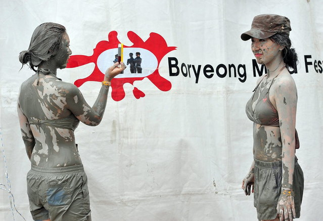 Tourists covered in mud take pictures during the 16th Boryeong mud festival at Daecheon swimming beach in Boryeong, 150 kilometers southwest of Seoul, on July 20, 2013. The annual festival which runs from July 19-28 aims to encourage the use of mud for cosmetic skin-care and to promote tourism in the region. (Photo by Jung Yeon-Je/AFP Photo)