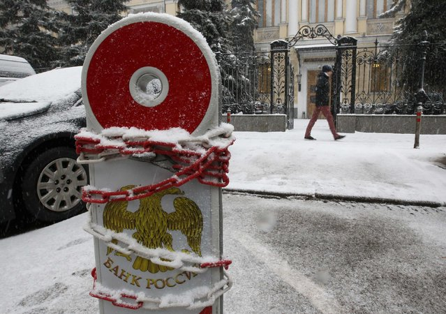 A chain is seen wrapped around a road sign for parking, with the coat of arms of the Central Bank seen on it, near the headquarters of the bank in central Moscow January 30, 2015. Russia's central bank cut its key interest rate by two points to 15 percent on Friday, as the economy slides towards recession because of a collapse in global oil prices and Western sanctions over the Ukraine crisis. (Photo by Grigory Dukor/Reuters)