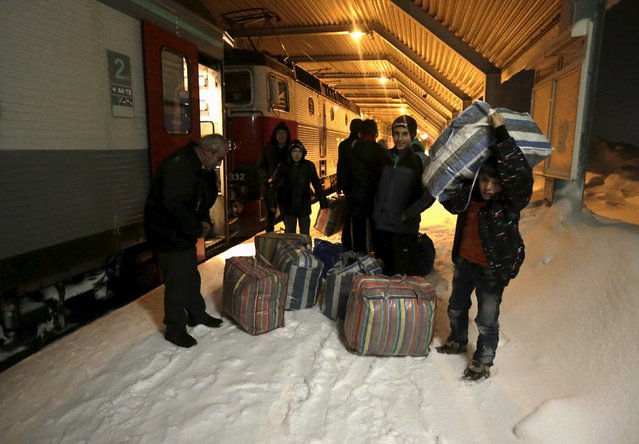 Refugees disembark and make their way to a camp at a hotel touted as the world's most northerly ski resort in Riksgransen, Sweden, December 15, 2015. (Photo by Ints Kalnins/Reuters)
