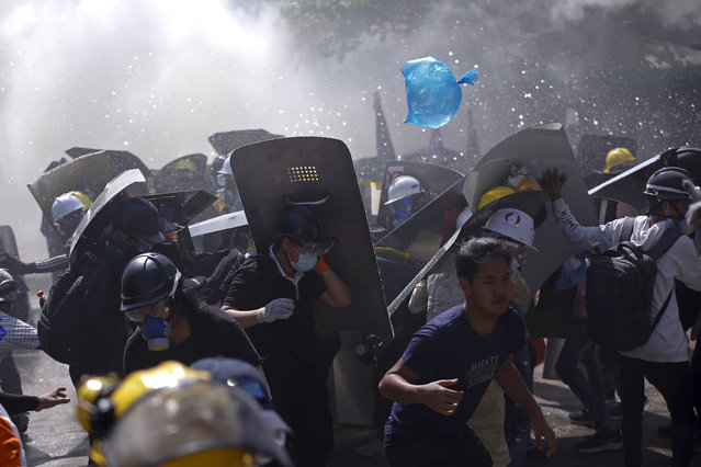 Protesters are dispersed as riot police fire tear gas during a demonstration in Yangon, Myanmar, Monday, March 8, 2021. (Photo by AP Photo/Stringer)