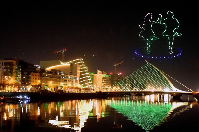 """A display by Tourism Ireland entitled """"Orchestra of Light"""" featuring a swarm of 500 drones is animated in the night sky above the Samuel Beckett bridge on the river Liffey for St Patrick's Day, as it is cancelled for the second year in a row due to the spread of coronavirus disease (COVID-19), in Dublin, Ireland, March 17, 2021. (Photo by Clodagh Kilcoyne/Reuters)"""