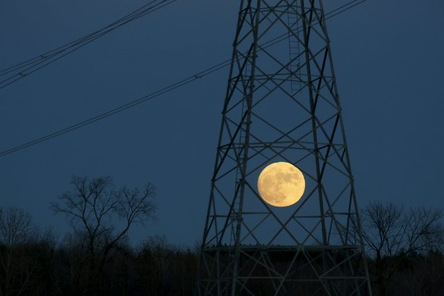 The full moon rises behind a hydro tower on Christmas eve in Ottawa December 24, 2015. Its appearance marks the first full moon to happen on Christmas day since 1977, and this phenomenon will not happen again until 2034, according to weather reports. (Photo by Blair Gable/Reuters)