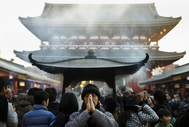 A man prays outside the Sensoji temple ahead of the New Year holidays in Tokyo, Japan December 30, 2015. (Photo by Thomas Peter/Reuters)