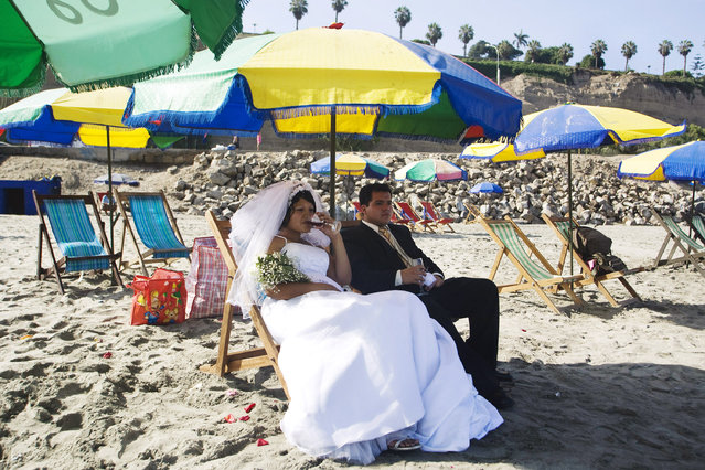 A bride and a groom rest before a ritual with shamans for Saint Valentine's Day at a beach in Lima Febraury 12, 2010. (Photo by Enrique Castro-Mendivil/Reuters)