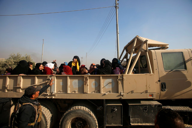 Displaced Iraqi people who left their homes ride in a military vehicle of Iraqi security forces during a battle with Islamic State militants in Mosul, Iraq, November 29, 2016. (Photo by Khalid al Mousily/Reuters)