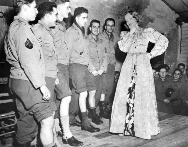 Screen actress Marlene Dietrich, left, tries to select the Queen of the chorus of the GI troupe during her visit to their camp at Namur, Belgium, November 30, 1944. The soldiers are, left to right: Cpl. Seaman Schlesinger, Philadelphia, Pa.; Sgt. Samuel Bonnvido, Warren, Pa.; Cpl. Thomas C. Vapehart, Indianapolis, Ind.; Pvt. Carl Fritz, Somersey, Pa.; Sgt. George Bagio, Cliffside Park, N.J., and Sgt. Dick Mullen, New York. (Photo by AP Photo)