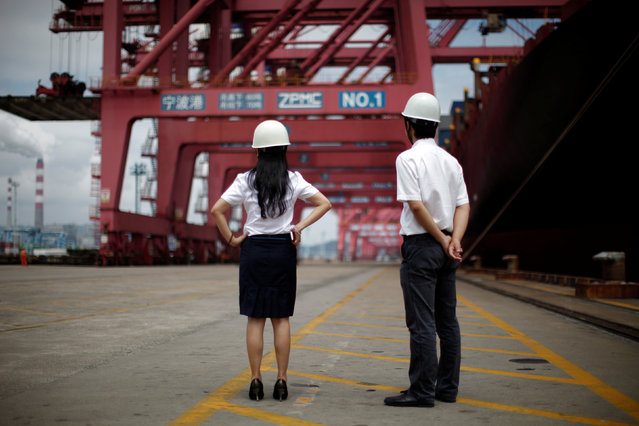 Employees stand next to a container ship at Ningbo port in Ningbo, Zhejiang province June 21, 2012. (Photo by Carlos Barria/Reuters)