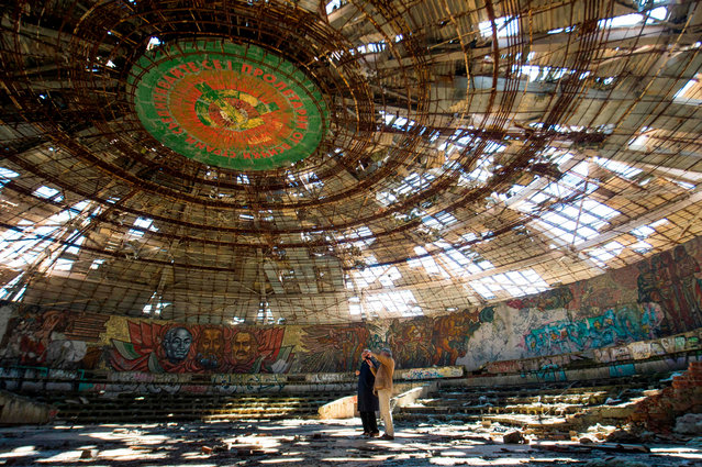 Experts from Europa Nostra, a NGO for protection and celebration of Europe' s cultural and natural heritage inspect the crumbling oval skeleton of the House of the Bulgarian Communist Party on mount Buzludzha in central Bulgaria on September 27, 2018. (Photo by Nikolay Doychinov/AFP Photo)