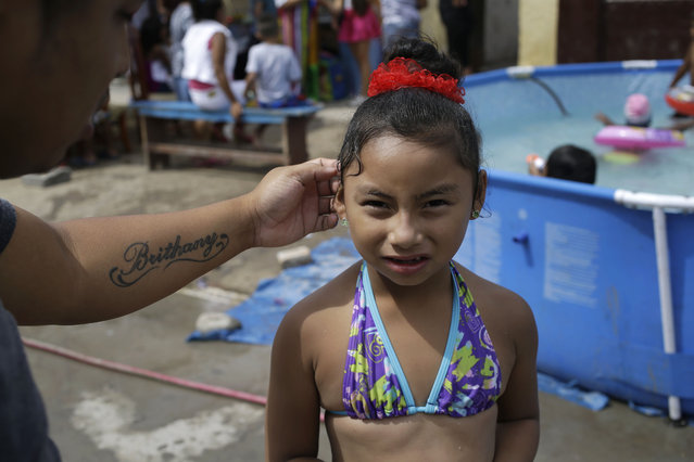 In this Sunday, February 15, 2015 photo, a father arranges loose hair strands behind his daughter's, Brithany, ear during a pool party in Callao, Peru. The heat in and around Peru's sprawling capital can be intense in February, the heart of the Southern Hemisphere's summer, and residents of its poor neighborhoods are cooling themselves by setting up plastic pools on the street in front of their homes. (Photo by Martin Mejia/AP Photo)