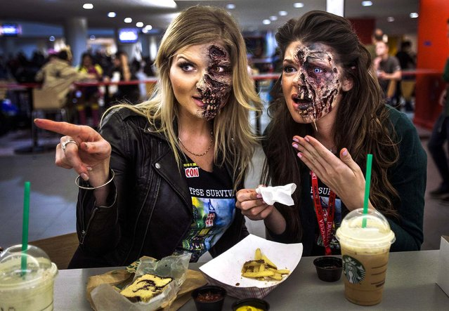 Makeup artists Kamila Wysocka and Alexis Jackson from Florida, point at another costumed person as they eat dinner in their zombie makeup at ComicCon in New York, on Oktober 10, 2013. (Photo by Carlo Allegri/Reuters)