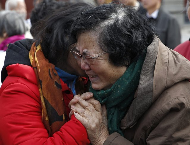 Wang Guohui (R), mother of Li Zhi, a passenger of the missing Malaysia Airlines flight MH370, cries next to another family member of a passenger during a gathering of family members of the missing passengers at Yonghegong Lama Temple in Beijing March 8, 2015. Prime Minister Najib Razak said on Sunday Malaysia remains committed to the search for the missing MH370 jetliner a year after it vanished without trace and he is hopeful it will be found.