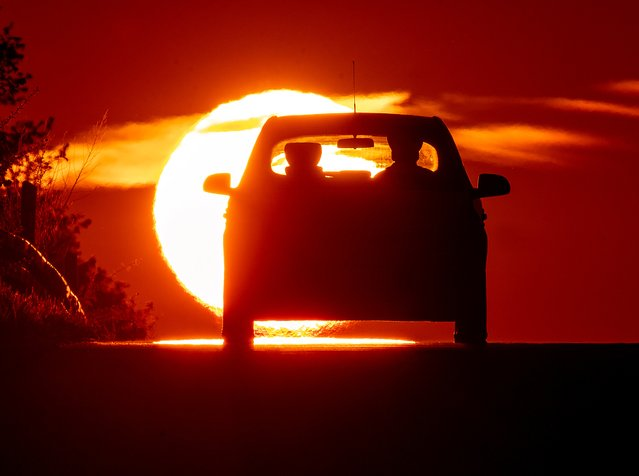 A car comes over a hill as the sun rises on the outskirts of Frankfurt, Germany, Monday, May 3, 2021. (Photo by Michael Probst/AP Photo)