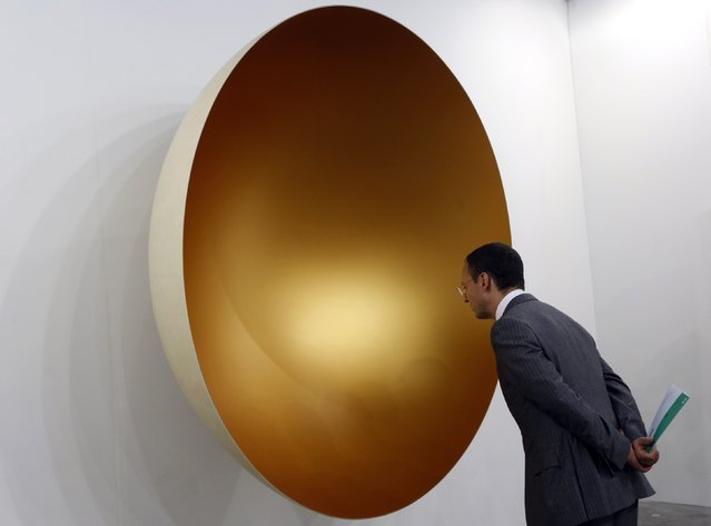 A visitor looks at an artwork by Indian sculptor Anish Kapoor at Art Basel's 2015 edition in Hong Kong March 13, 2015. (Photo by Bobby Yip/Reuters)