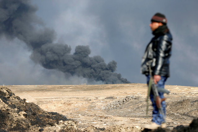 A policeman stands in front of oilfields burned by Islamic State fighters in Qayyara, south of Mosul, Iraq  December 21, 2016. (Photo by Ammar Awad/Reuters)