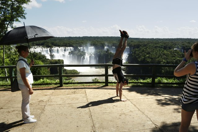 In this March 14, 2015 photo, a tourist poses for pictures doing a handstand at Iguazu Falls in Brazil. The falls are in the middle of thick jungle that has more than 1,000 plant and hundreds of animal species. Millions of tourists visit the falls each year on both sides of the border. (Photo by Jorge Saenz/AP Photo)