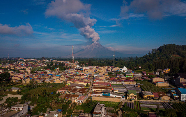 This aerial photo taken on May 10, 2021 shows Mount Sinabung spewing hot ash and smoke into the sky, seen from Karo, North Sumatra. (Photo by Tibta Nangin/AFP Photo)