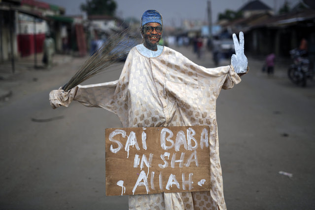 "A puppet showing Presidential challenger  Muhammadu Buhari is set at an intersection in Kaduna,  Nigeria Monday, March 30, 2015. Nigerians are waiting in hope and fear for results of the tightest and most bitterly contested presidential election in the nation's turbulent history. Placard reads ""He is the one god willing"". (Photo by Jerome Delay/AP Photo)"