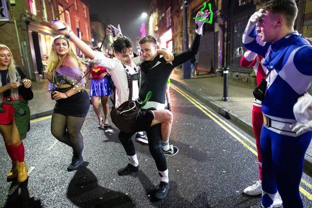 Two men dance on King Street, Wigan, UK on December 26, 2018. Revellers in Wigan enjoy Boxing Day drinks and clubbing in Wigan Wallgate. In recent years a tradition has been established in which people go out wearing fancy-dress costumes on Boxing Day night. (Photo by Joel Goodman/London News Pictures)