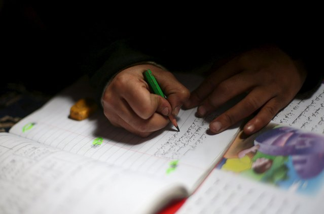 Hadeel, 10, the daughter of Shahrour, does her homework at her home in the besieged town of Arbeen, in Damascus suburbs, Syria February 6, 2016. (Photo by Bassam Khabieh/Reuters)