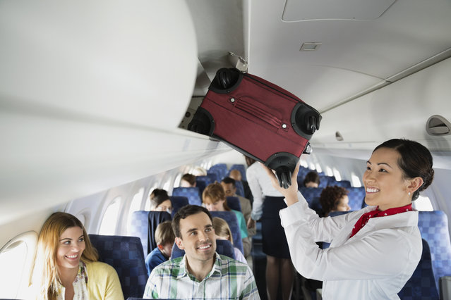 Flight attendant putting luggage in overhead bin in airplane. (Photo by Getty Images/Hero Images)