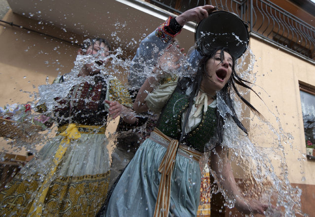 A young Slovak dressed in traditional costume (C) throws a bucket of water over a girl as part of Easter celebration in the village of Trencianska Tepla, north-western Slovakia, on April 6, 2015. Slovakia's men splash women with water and hit them with a willow to symbolize youth, strength and beauty for the upcoming spring season. (Photo by Samuel Kubani/AFP Photo)