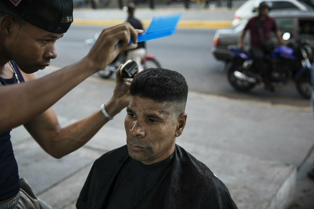 Kevin Cedeno, left, cuts the hair of Silvio Villaroel, at a makeshift barber shop on a sidewalk in Caracas, Venezuela, Friday, January 25, 2019. Cedeno charges 1000 bolivars or around .50 cents US for each service. Juan Guaido, the Venezuelan opposition leader who has declared himself interim president, appeared in public Friday for the first time in days and vowed to remain on the streets to usher in a transitional government, while President Nicolas Maduro dug in and accused his opponents of orchestrating a coup. (Photo by Rodrigo Abd/AP Photo)