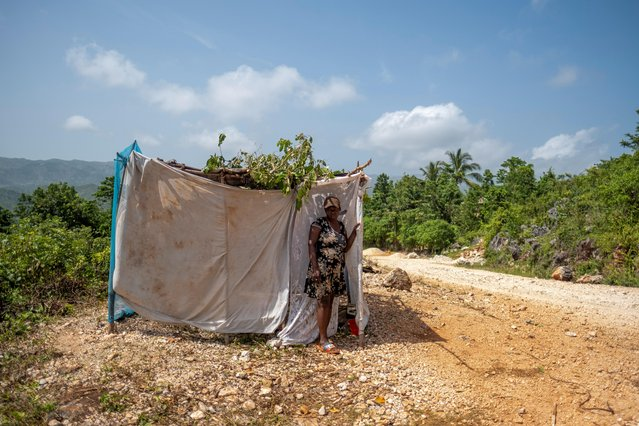 A woman stands in front of her makeshift tent in the Nan Konsey neighborhood in Pestel, Haiti on August 23, 2021. (Photo by Ricardo Arduengo/Reuters)