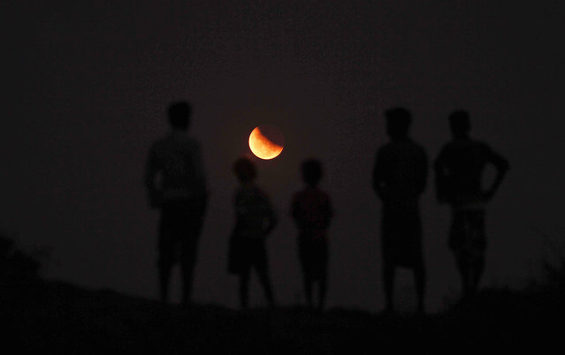Indians watch a lunar eclipse from the banks of River Kuakhai on the outskirts of Bhubaneswar, India, Saturday, April 4, 2015. (Photo by Biswaranjan Rout/AP Photo)