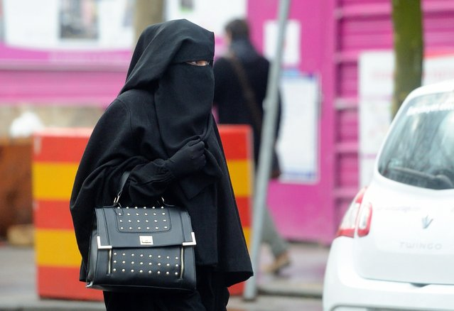 A woman wearing a niqab, a type of full veil, as she walks in a street in the center of Roubaix, northern France, on January 9, 2014. (Photo by Philippe Huguen/AFP Photo)