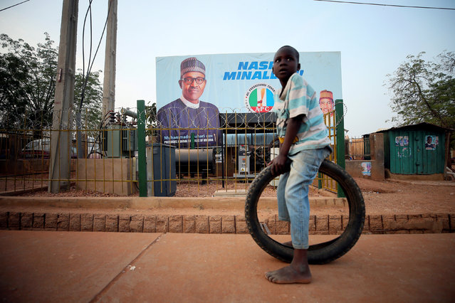 A boy sits on a tyre in front of a billboard on the eve of Nigeria's 2019 presidential election in Daura, Katsina State, Nigeria February 22, 2019. (Photo by Afolabi Sotunde/Reuters)