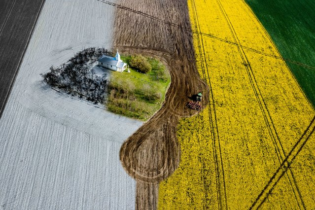 Four Seasons. Urban Commended. A lonely chapel in the middle of a field shot in the four seasons. This is the fifth in this series. A tractor is working the field. (Photo by Ovi D. Pop/Drone Photography Awards 2021)