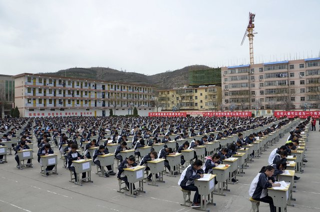 Students take an examination on an open-air playground at a high school in Yichuan, Shaanxi province April 11, 2015. (Photo by Reuters/Stringer)