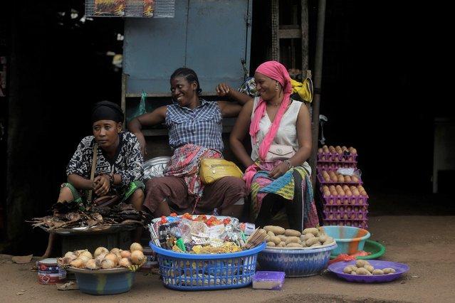 Women sells onions and potatoes at Kaporo market in Conakry, Guinea Monday, September 13, 2021. (Photo by Sunday Alamba/AP Photo)