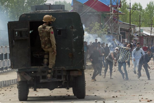 An Indian policeman takes cover behind an armored car as Kashmiri protestors hurl rocks and bricks in Narbal, some 15 Kilometers (10 miles) North of Srinagar, Indian controlled Kashmir, Saturday, April 18, 2015. Government forces fired on anti-India protesters Saturday and killed a teenage student on the second day of violent clashes in the disputed Himalayan region, police said. (Photo by Dar Yasin/AP Photo)