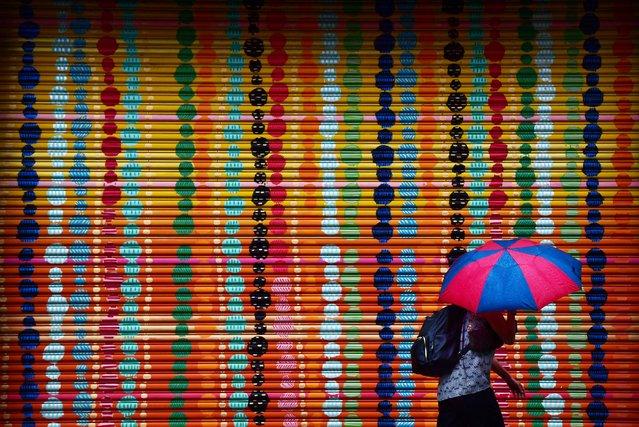 A pedestrian passes a colorfully painted door as rain falls in Alexandria, Va. on September 20, 2018. (Photo by Matt McClain/The Washington Post)