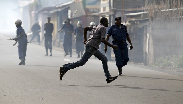 A man runs as riot police disperse residents participating in street protests against the decision made by Burundi's ruling National Council for the Defence of Democracy-Forces for the Defence of Democracy (CNDD-FDD) party to allow President Pierre Nkurunziza to run for a third five-year term in office, in the capital Bujumbura, April 26, 2015. (Photo by Thomas Mukoya/Reuters)