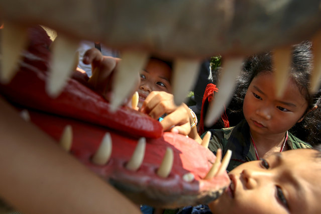 Children play with a dinosaur statue during the Children's Day celebration at Government House in Bangkok, Thailand, January 14, 2017. (Photo by Athit Perawongmetha/Reuters)
