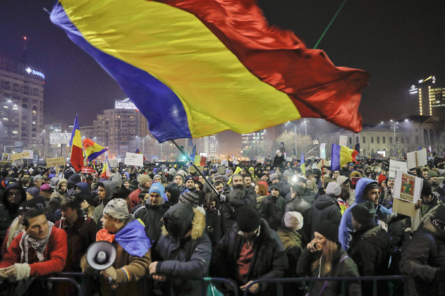 A man waves a large Romanian flag during a protest joined by tens of thousands against a government decree that dilutes what qualifies as corruption, in Bucharest, Romania, Thursday, February 2, 2017. Huge protests erupted in the capital and spread to cities around Romania in the past two nights after the government changed the law – one of the biggest protests in Romania since communism ended in 1989. (Photo by Vadim Ghirda/AP Photo)