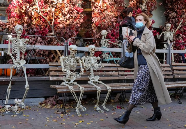 A woman wearing in face mask to curb the spread of COVID-19 passes street's cafe in Kyiv, Ukraine, Friday, October 22, 2021. Coronavirus infections and deaths in Ukraine have surged to all-time highs amid a laggard pace of vaccination, which is one of the lowest in Europe. (Photo by Efrem Lukatsky/AP Photo)