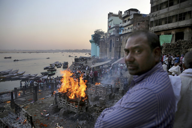 In this March 19, 2019, photo, funeral pyres burn on the banks of river Ganges, in Varanasi, India. According to ancient practice, funeral pyres burn constantly, with the debris and ash shoveled into the river. In the Indian city considered the center of the Hindu universe, Prime Minister Narendra Modi has commissioned a grand promenade connecting the sacred Ganges river with a centuries-old temple dedicated to Lord Shiva, the god of destruction. (Photo by Altaf Qadri/AP Photo)