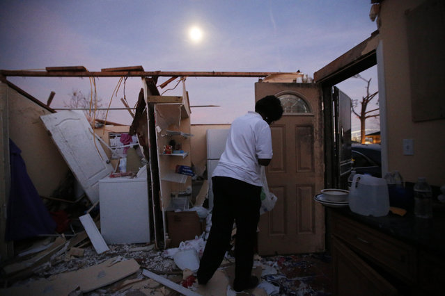 With a moon rising overhead, Theresa Perkins retrieves some belongings from inside of the destroyed home of her friend Thelma Packnett, in the aftermath of Tuesday's tornado that tore through the New Orleans East section of New Orleans, Wednesday, February 8, 2017. (Photo by Gerald Herbert/AP Photo)