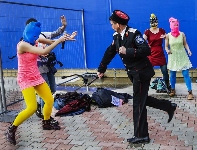 A Cossack militiaman attacks Nadezhda Tolokonnikova and a photographer as she and fellow members of the punk group p*ssy Riot, including Maria Alekhina, right, in the pink balaclava, stage a protest performance in Sochi, Russia, on February 19, 2014. (Photo by Morry Gash/Associated Press)