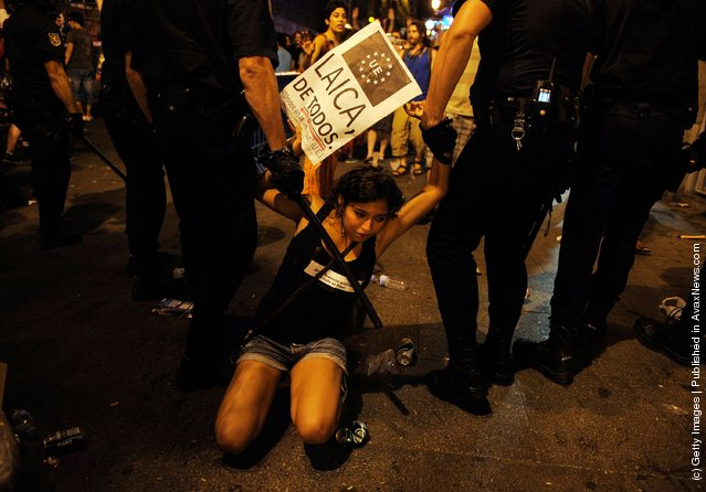 A girl is moved on by police after disturbances during a protest against the World Youth Day 2011 celebrations