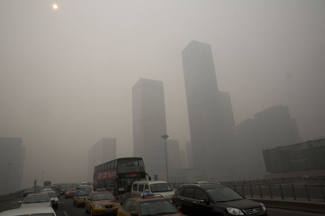 Vehicles clog a highway during a hazy day in Beijing, China, Wednesday, February 26, 2014. Beijing remained cloaked in hazardous white pollution hiding much of its skyline Wednesday, despite the announced closures or production cuts at 147 of the city's industrial plants. (Photo by Ng Han Guan/AP Photo)