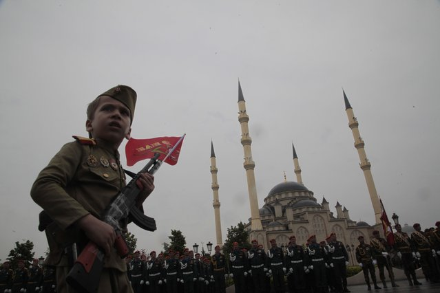 A boy wearing a Soviet era uniform carries a toy gun as he walks past a mosque during celebrations marking the 70th anniversary of the victory over Nazi Germany, in Chechnya's provincial capital Grozny, Russia, Saturday, May 9, 2015. (Photo by Musa Sadulayev/AP Photo)
