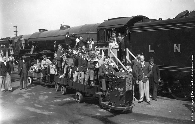 A miniature truck carrying a party of children in open carriages next to a London and North Eastern railway steam engine on a platform at Ilford railway station