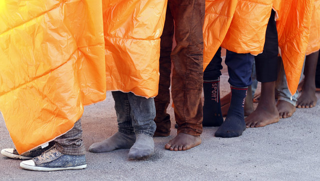 Migrants stand in line after disembark from the Norwegian vessel Siem Pilot at Pozzallo's harbour, Italy, March 29, 2016. (Photo by Antonio Parrinello/Reuters)