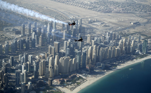 An aerial view taken from behind airplane's window glass shows Swiss pilot and aviation enthusiast Yves Rossy(Bottom) known as the Jetman and French Vince Reffett (Up) flying over Jumeirah Beach Residence (also known as JBR)  in Dubai, United Arab Emirates on 12 May 2015. (Photo by Ali Haider/EPA)